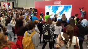 Visitantes que prueban el videojuego del baile de Nintendo almacen de video