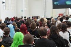 Visitantes que sentam e que olham a fluência na tela de projeção Fotos de Stock Royalty Free