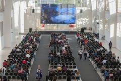 Visitantes que sentam e que olham a fluência na tela de projeção Imagem de Stock