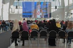 Visitantes que sientan y que miran fluir en la pantalla de proyección Imagen de archivo