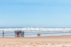 Visitantes que toman una foto del grupo en una playa Imagenes de archivo