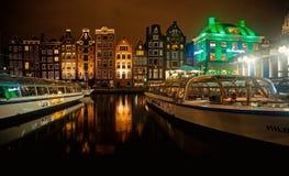 Visite barcos no canal de rio e construções históricas em Amsterdão fotografia de stock