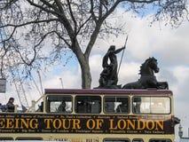 Visite guidée à couvercle serti d'autobus de Londres se déplaçant près du char de statue de Boadicea Images libres de droits