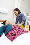 Visite heureuse de grand-mère malade par la petite-fille Photos libres de droits