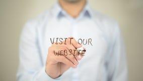 Visite nuestro sitio web, escritura del hombre en la pantalla transparente Fotografía de archivo libre de regalías