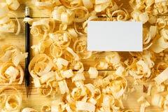 Visitenkarte auf Holztisch für Tischlerwerkzeuge mit Sägemehl Lizenzfreies Stockfoto