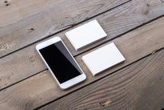 Visitenkarten und Smartphone lokalisiert auf altem hölzernem Hintergrund Lizenzfreies Stockbild