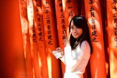 Visiteur asiatique prenant la photo aux portes rouges de Torii Image stock