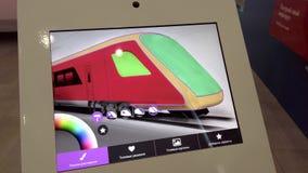 Visiteur d'exposition choisissant la couleur de futurs trains sur un comprimé avec un écran tactile banque de vidéos