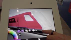 Visiteur d'exposition choisissant la couleur de futurs trains sur un comprim? avec un ?cran tactile banque de vidéos
