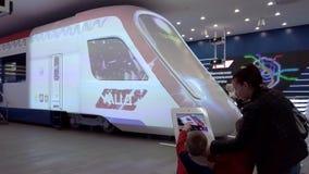Visiteur d'exposition choisissant la couleur de futurs trains sur un comprim? avec un ?cran tactile clips vidéos