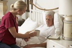Visiteur de santé donnant la boisson chaude masculine supérieure dans le lit à la maison Images libres de droits