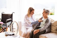 Visiteur de santé et une femme supérieure pendant la visite à la maison photo stock