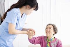 Visiteur de santé et une femme supérieure pendant la visite à la maison image libre de droits