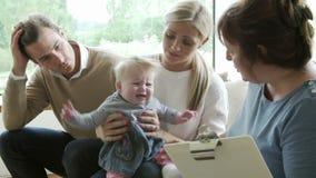 Visiteur de santé parlant à la famille avec le jeune bébé clips vidéos
