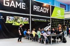 Visiteurs examinant de nouveaux jeux et nouvelles cartes vidéo dans la région de Nvidia photographie stock libre de droits