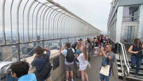 Visiteurs observant le paysage urbain de Manhattan à la plate-forme d'observation d'Empire State Building banque de vidéos