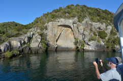 Visiteurs photographiant Maori Rock Carving iconique au Tau de lac Photographie stock libre de droits