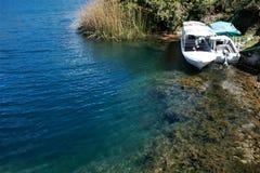 Visiti Laguna messo in bacino barche Cuicocha che mostra che ripido diminuisca nel lago dal litorale immagini stock
