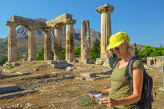 Visiting Ancient Corinth. Tourism travel concept. Greece tourist female reads travel guide outdoors. Happy woman holding informative guide at Doric Temple of Stock Photography