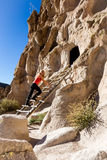 Visiting the ancient ruins in Bandelier National Monument. Beautiful woman climbing into caves in Bandelier national Monument in New Mexico Royalty Free Stock Photography