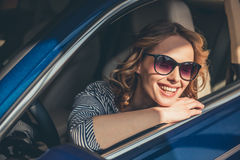 Visiting car dealership. Beautiful young woman in sun glasses is looking at camera and smiling while sitting in a new car in car dealership Royalty Free Stock Images