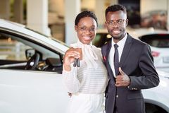 Visiting car dealership. couple holding key of their new car, looking at camera. Visiting car dealership. Beautiful african couple is holding a key of their new Royalty Free Stock Images