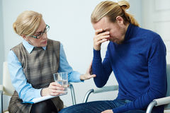 Visiting counselor. Frustrated young men sharing his problem with counselor stock image