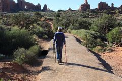 Visiting Double Arches at Arches National Park. Lady carrying a tripod and a walking stick down a paved trail at Arches National Park Stock Image