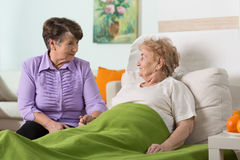 Visiting a friend. Woman visiting her sick elderly friend Royalty Free Stock Images