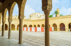 Visiting the Grand Mosque. SOUSSE, TUNISIA - SEPTEMBER 6, 2015: The arcades of the Grand Mosque give shade in hot midday, on September 6 in Sousse Stock Photos