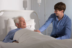 Visiting grandfather in hospital. Grandson is visiting his grandfather recovering in hospital Royalty Free Stock Photo