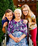 Visiting Grandmother. Teenager grandchildren visiting their old disabled grandmother Stock Images