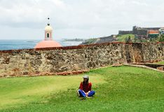 Visiting Puerto Rico. The girl having a rest on a grass next to El Morro fort wall in the old town of San Juan, the capital of Puerto Rico Royalty Free Stock Photos