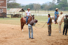 Visiting rural farmland. PAK CHONG, KORAT, THAILAND - JANUARY 15 : The unidentified cowboys are teaching tourists how to ride a horse on January 15, 2012 at Chok stock photos