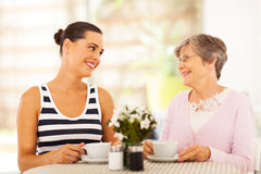 Visiting senior mother. Young women visiting senior mother and having coffee together Royalty Free Stock Image