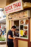 Visitor buying a Thai meal. A visitor at the famous Waikele Premium Outlets, Honolulu, Hawaii, USA, buying Thai food. This venue has a small open-air food court Stock Photos