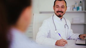 Visitor consulting smiling man doctor stock footage