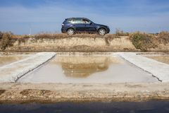 Visitor driving beside Isla Cristina saltworks, Spain Stock Photography