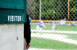 Visitor Dugout. A green baseball dugout, with a coach's arm just visible at the entrance, and a youth baseball game being played in the background stock image
