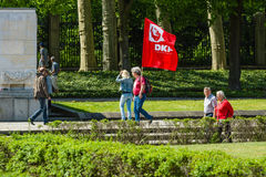 A visitor with the flag of the German Communist Party. BERLIN - MAY 08, 2016: Victory in Europe Day. Soviet War Memorial and military cemetery in Berlin's royalty free stock photos