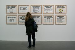 An artwork by Guerrilla Girls in the famous Tate Modern in London. A visitor in front of an artwork of Guerrilla Girls. A framed artwork in the famous Tate Stock Photos