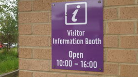 Visitor information booth sign on brick wall stock video