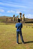 Visitor looking at the 15 huge Moai statues of Ahu Tongariki, Archaeological site on Easter Island, Chile. South America admiring adventure amazing awesome royalty free stock image