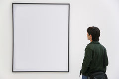 Visitor looks on frame. On white wall Royalty Free Stock Images
