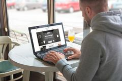 Visitor open a responsible website of the design company on his laptop. Coffee shop in background Stock Photography