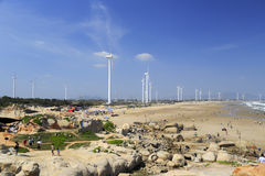 Visitor play on the sand stone beach under wind turbine Royalty Free Stock Images