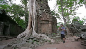 Visitor reading tourist information map in Ta Prohm temple, angkor stock video