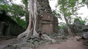 Visitor reading tourist information map in Ta Prohm temple, angkor stock video footage