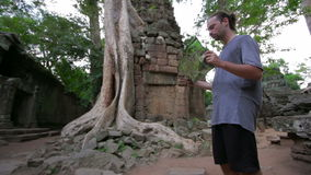 Visitor reading tourist information map in Ta Prohm temple, angkor Stock Photos
